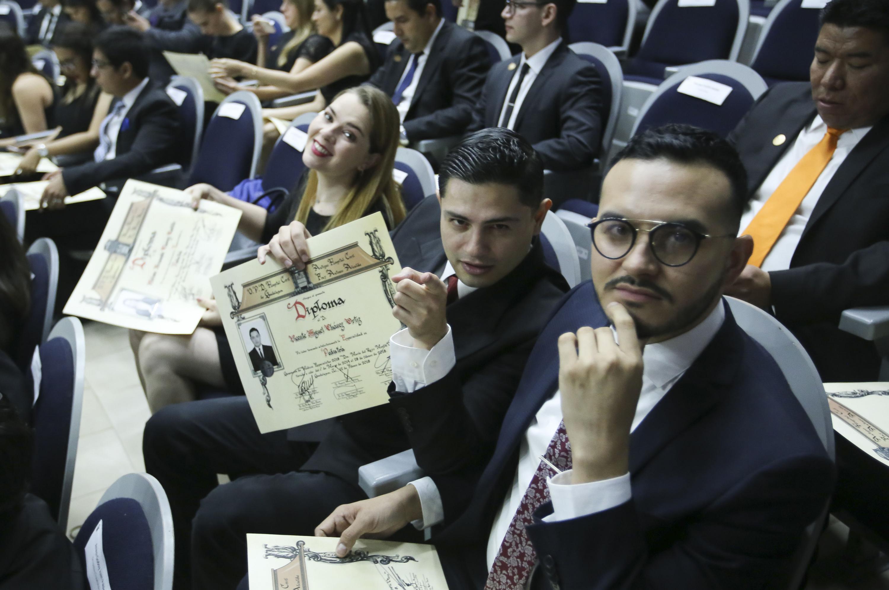3 egresados (Una mujer y dos hombres) muestran su diploma de acreditación
