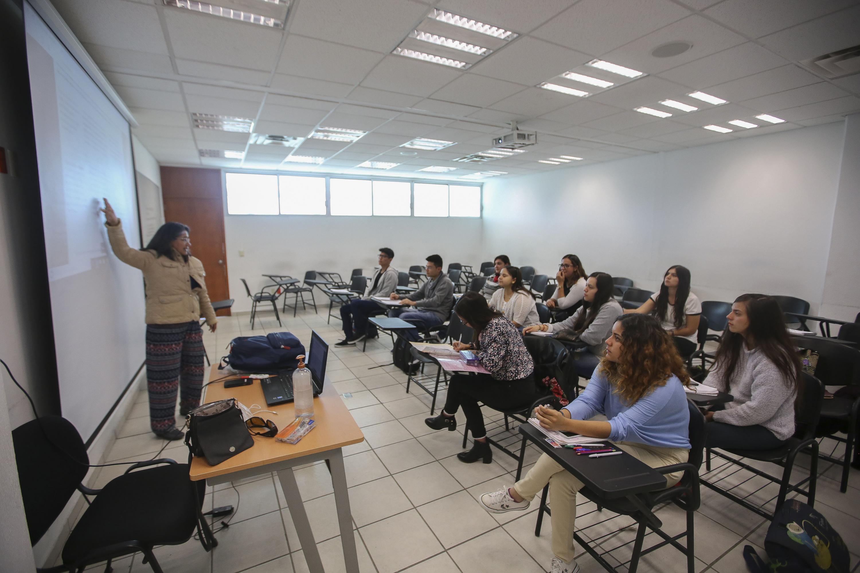 Profesora del CUCSH, impartiendo clases con apoyo del proyector del aula.