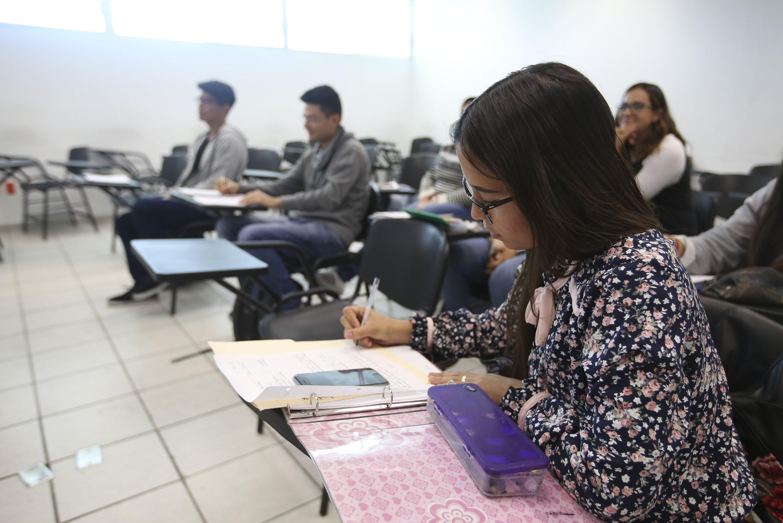 Alumna del Centro Universitario de Ciencias Sociales y Humanidades (CUCSH), tomando notas de la clase.