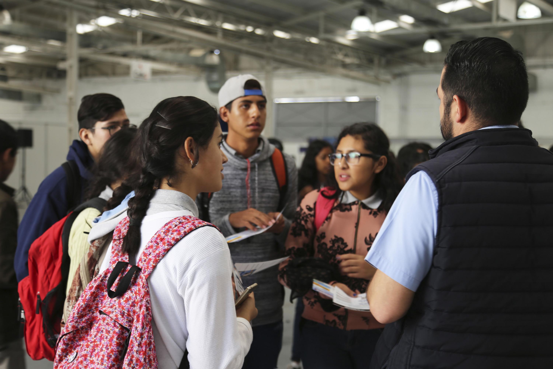 Grupo de estudiantes con folletos de información en la mano de la expo profesiones 2018.