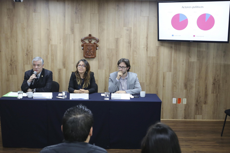 Los tres academicos hablando desde la mesa de presentación y una pantalla muestra una gráfica de pay