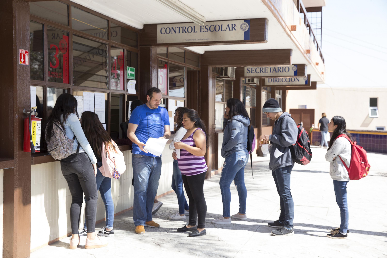 Alumnos haciendo fila en control escolar de un centro universitario
