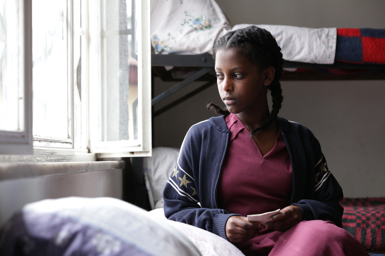 """Adolescente de tez morena, sentada en una cama y viendo a través de la ventana, escena de la película """"Difret""""."""