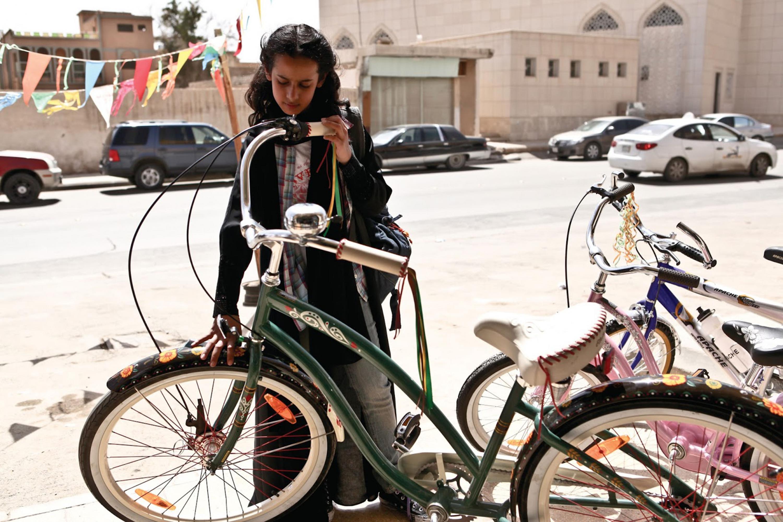 """Niña observando una bicicleta, escena de la película """"La bicicleta verde""""."""