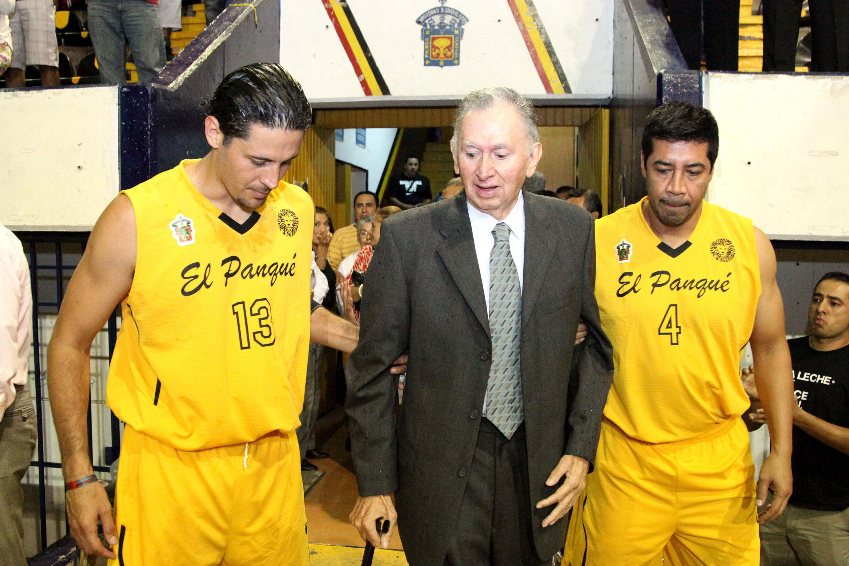 """Dos jugadores de la selección de basquetbol de la UdeG ayudando a caminar a Ramiro Vázquez Gutiérrez, el """"Genio"""""""