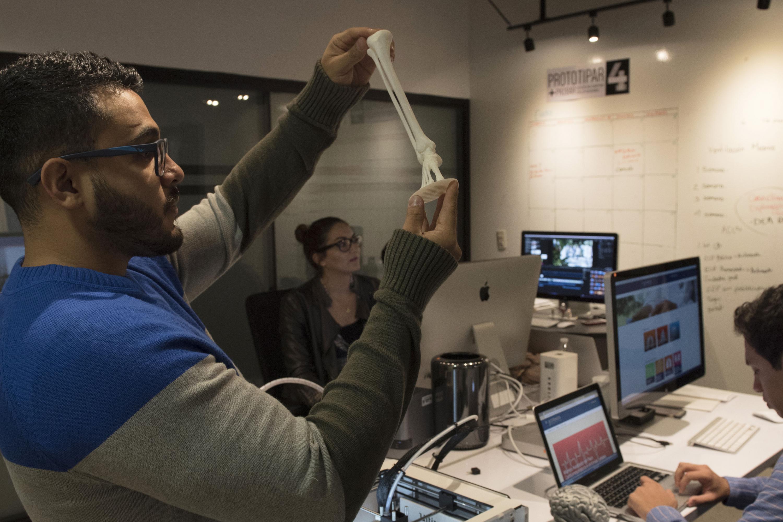3 jovenes trabajando en un laboratorio de prototipos y uno sostiene un modelo 3D de un hueso. Imagen de archivo