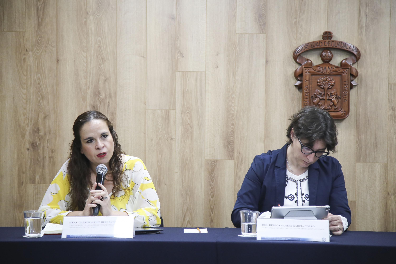 Maestra Gabriela Ruiz Hernández, coordinadora de la carrera en Periodismo del CULagos, con micrófono en mano haciendo uso de la voz.