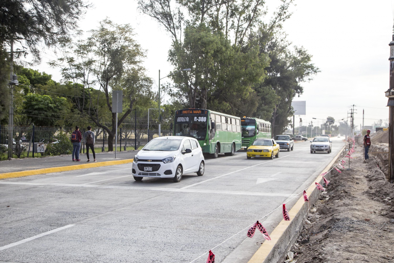 Vehiculos particulares y dos unidades de transporte publico pasan al lado de las obras del periférico