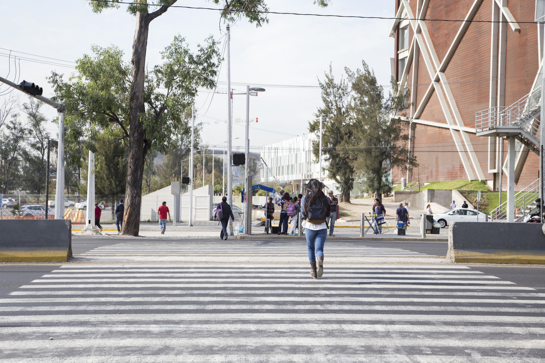 Una estudiante cruzando el periferico por el paso peatonal. de fondo la Biblioteca Pública del Estado de Jalisco