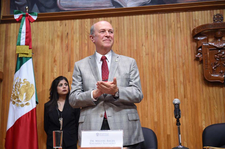 Doctor Miguel Ángel Navarro Navarro, nuevo Rector General sustituto, de pie y aplaudiendo ante los miembros del Consejo General Universitario, en el Paraninfo Enrique Díaz de León.