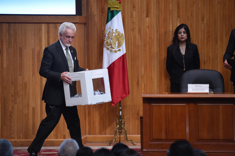 Mtro. José Manuel Jurado Parres, director de la preparatoria No. 5, portando la urna con las votaciones emitidas por el Consejo General Universitario para su conteo.