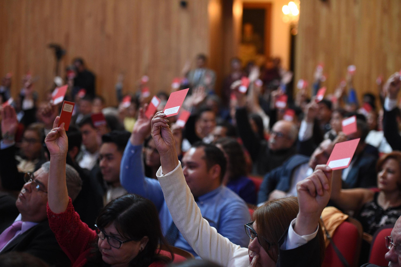 Miembros del Consejo General Universitario realizando su voto para la toma de decisiones.