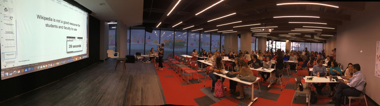 Panoramica del salon en donde hay una proyeccion en pantalla y los academicos hablan entre si