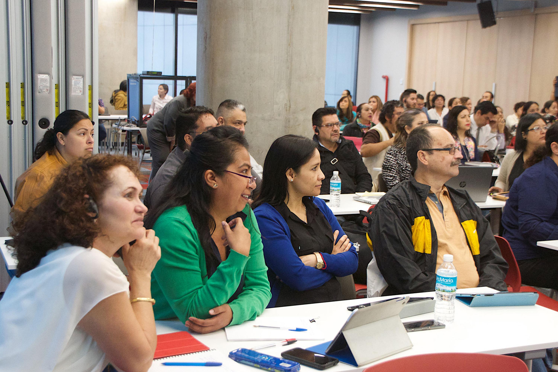 Academicos escuchando al presentador con ayuda de audifonos para traducción