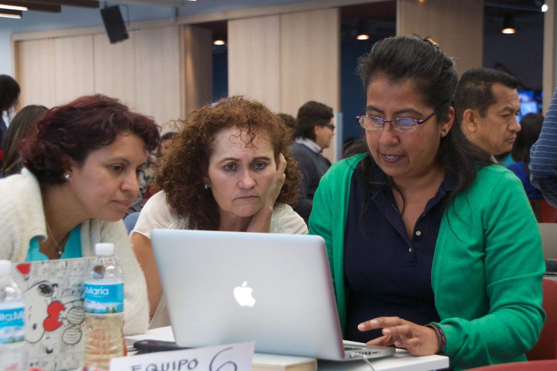 Tres profesoras  trabajando con una computadora portatil durante el curso