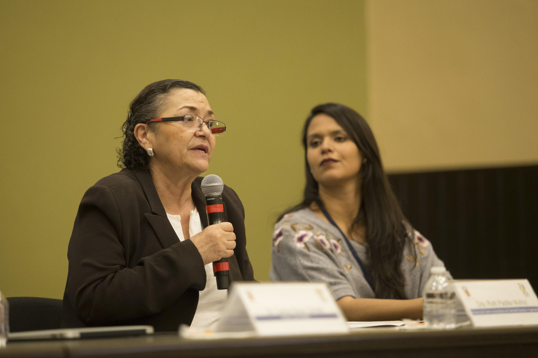 Doctora Ruth Padilla Muñoz, Rectora del Centro Universitario de Ciencias Exactas e Ingenierías, con micrófono en mano haciendo uso de la voz.