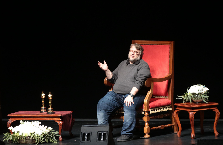 Guillermo del Toro sentado en la silla roja del escenario