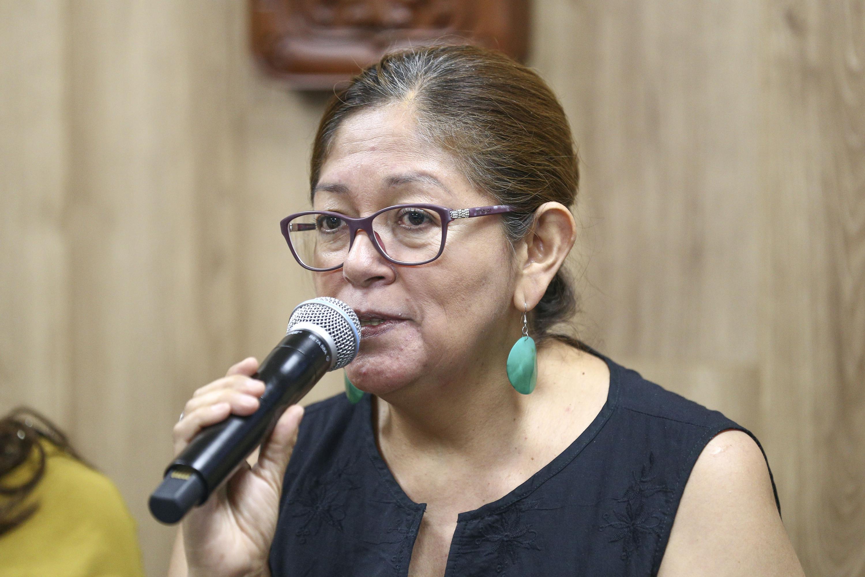 Doctora Yolanda Campos hablando frente al micrófono en rueda de prensa