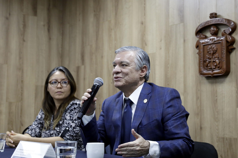 Doctor Armando Zacarías Castillo, Jefe del Departamento de Estudios Políticos, del CUCSH; con micrófono en mano haciendo uso de la palabra durante rueda de prensa.