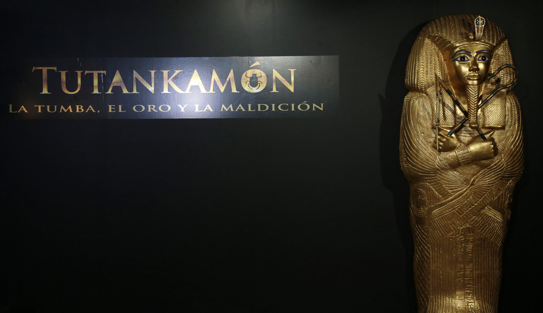 Letrero de la exposición -Tutankamón, la tumba, el oro y la maldición-; y la replica de su ataúd con terminación en chapa de oro.