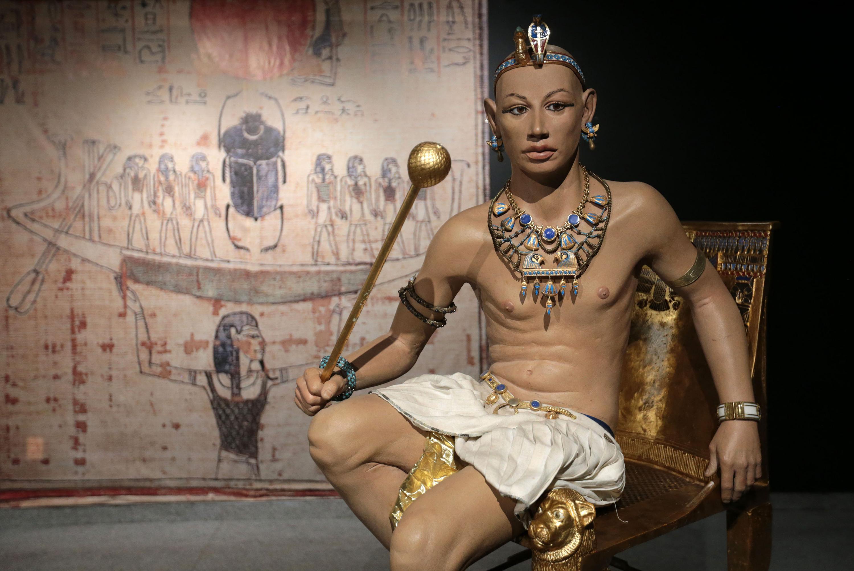 Estatua del faraón egipcio Tutankamón, sentado sobre su trono terminado en chapa de oro y de fondo un mural de la época.