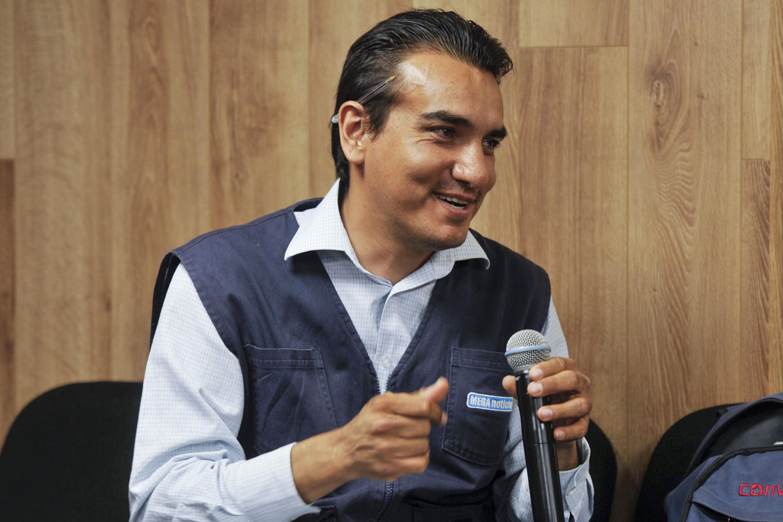 Reportero de Mega noticias,con micrófono en mano haciendo uso de la voz