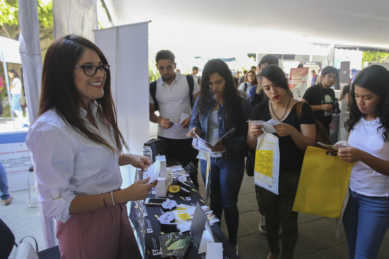 Jovenes del CUCEA recibiendo información de uno de los expositores