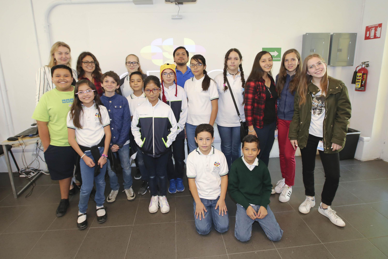 Fotografía grupal de trece niños y cuatro instructores del taller