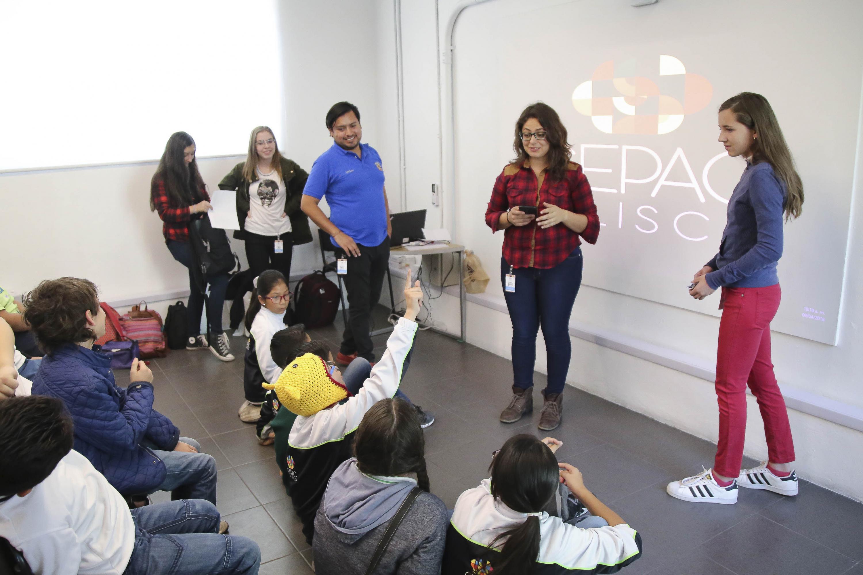 En el taller los niños haciendo preguntas a una joven instructora