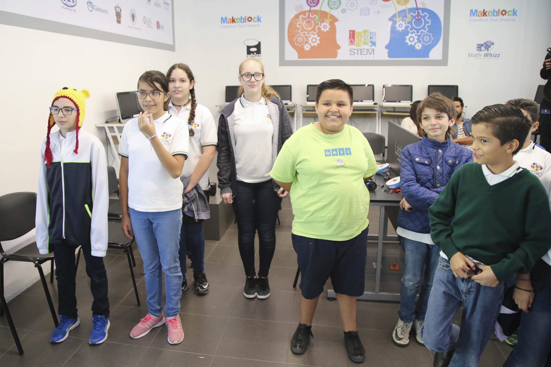 Algunos niños participantes de pie escuchan a un coordinador del taller