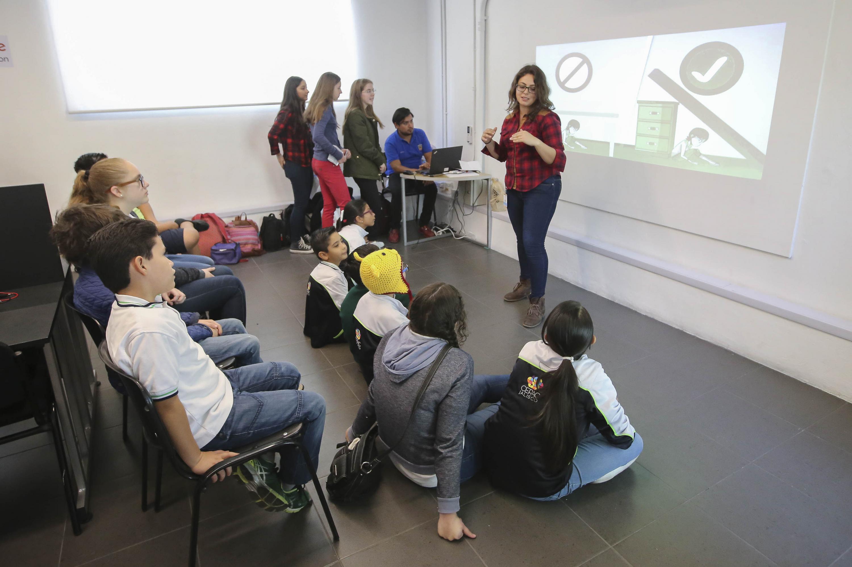 En el taller una joven instructora de lentes responde expone a los niños participantes