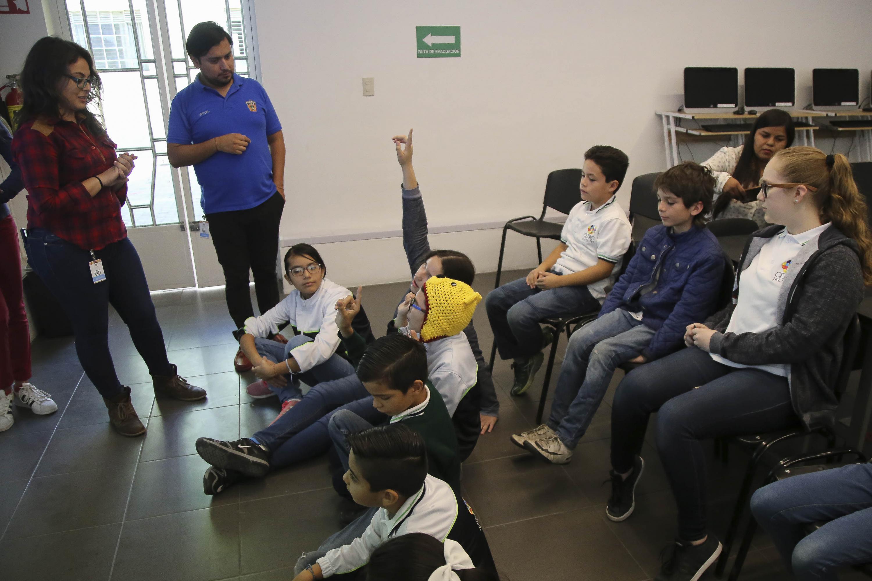 Dos niños levantan la mano mientras hablan con los instructores que los escuchan de pie