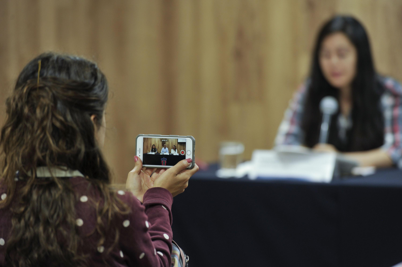 Asistente a rueda de prensa, videograbando con su celular la rueda de prensa.