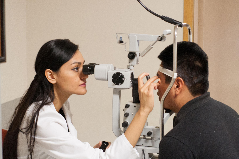 Médico Oftalmólogo revisando los ojos de un paciente.