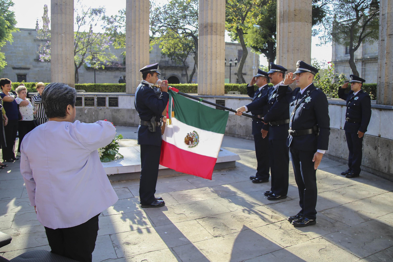 Comunidad universitaria haciendo saludo a la bandera, mientras que los cadetes extienden la bandera.