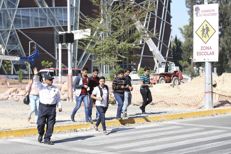 Agente vial cediendo el paso a un grupo de peatones que cruzan el Periférico norte.