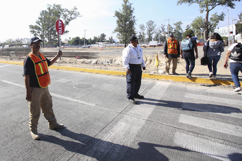 Agente Vial y Banderero, deteniendo el trafico vehicular, para que los estudiantes circulen con seguridad.