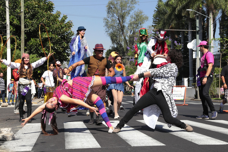 Jovenes disfrazados desfilando por una calle del centro de Guadalajara