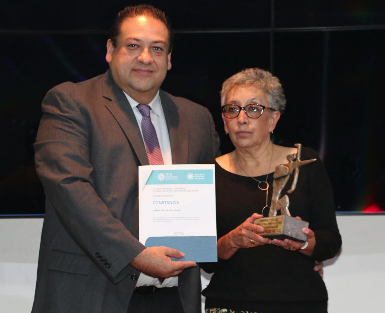 El rector de CUNORTE haciendo entrega del reconocimiento y trofeo a la doctora Arias Roza