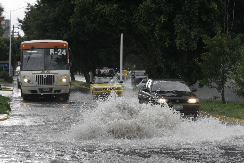 Camiones del transporte público y automovilistas, transitando por calles inundadas.