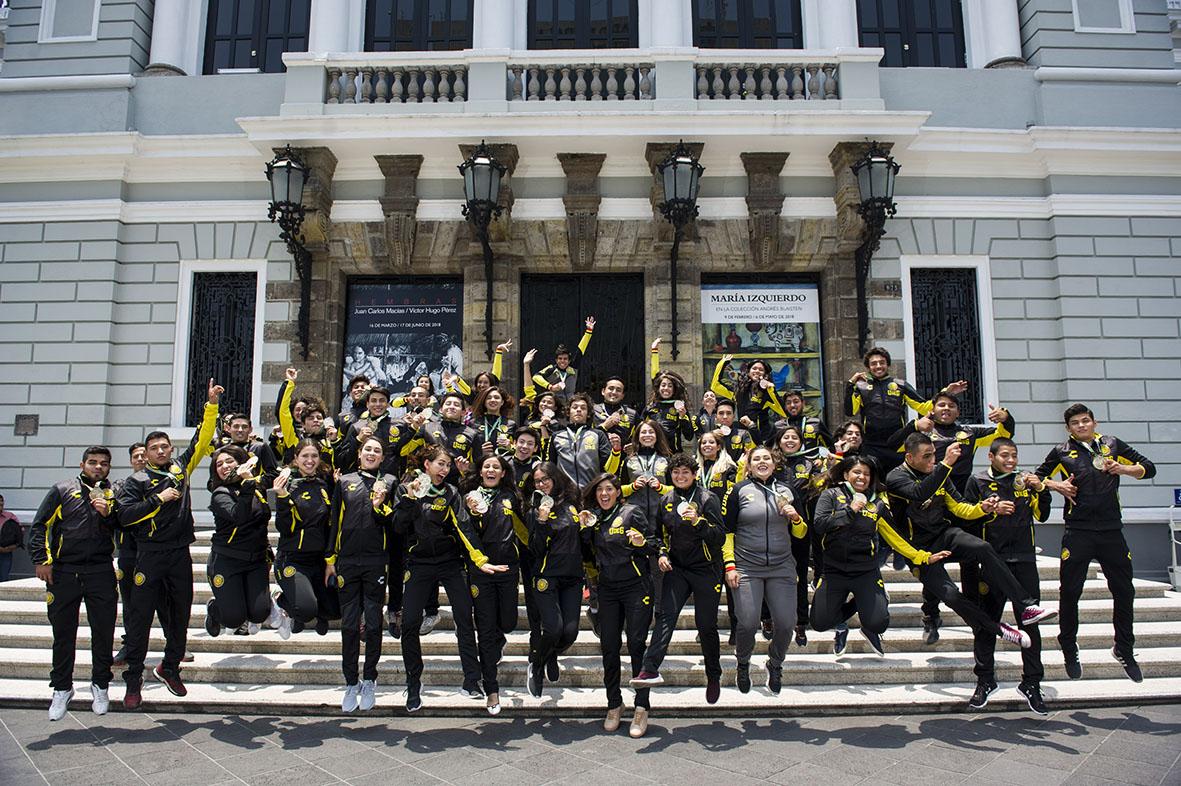 Equipo de medallistas de la Universiada Nacional, en las afueras del Museo de las Artes, festejando con un salto su triunfo y participación.
