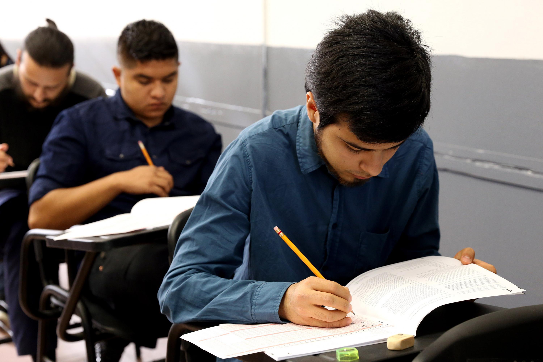 Aspirantes realizando la Prueba de Aptitud Académica, con lápiz, sacapuntas y borrador en mano.