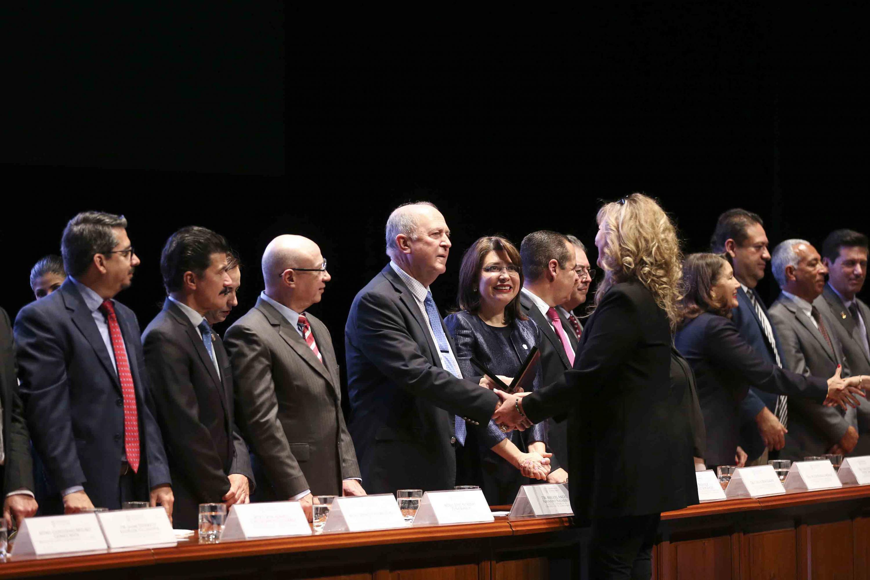 Rector General de la UdeG, doctor Miguel Ángel Navarro Navarro haciendo entrega de reconocimiento a una maestra