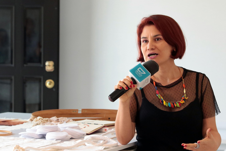 La escultora Andrea Rey, artista en residencia en el Museo de las Artes, de la Universidad de Guadalajara, con micrófono en mano, haciendo uso de la palabra.