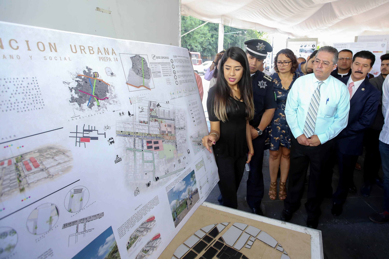 Una joven estudiante explica a los invitados de honor su proyecto urbanistico en la Rambla Cataluña