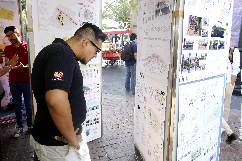 Un joven mira con detenimiento uno de los carteles de proyectos de Urbanistica en la exposicion
