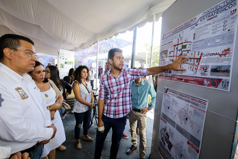 Un joven estudiante explica a los visitantes su proyecto arquitectonico