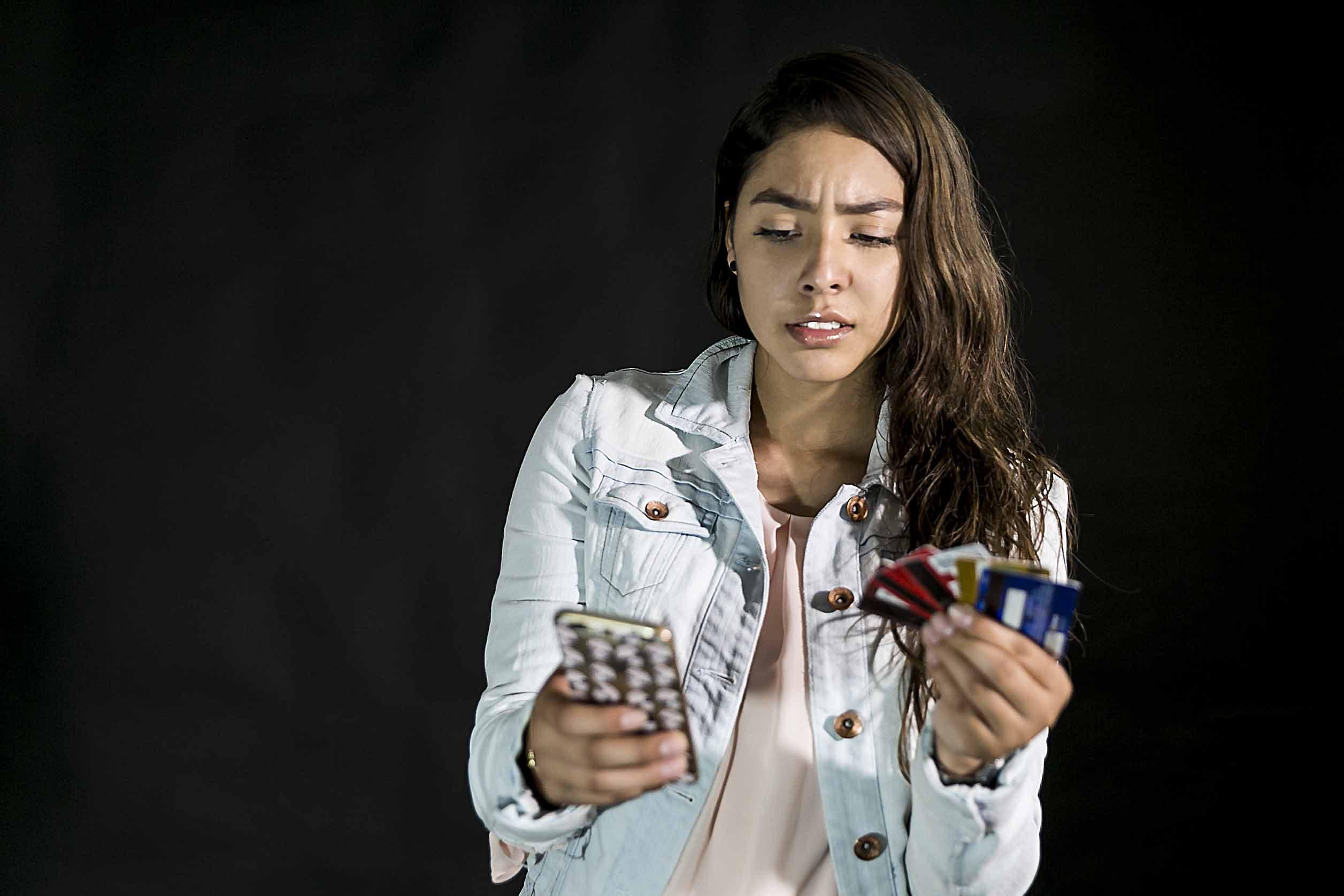 Joven sosteniendo sus tarjetas bancarias y utilizando su teléfono celular con preocupación.