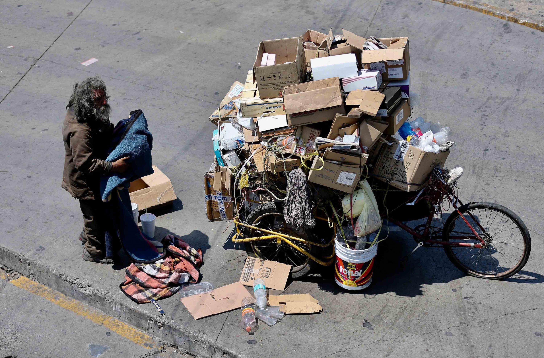 Persona en situación de calle, recogiendo sus cobijas mientras está enfrente de su triciclo de carga repleto de cartón que ha recogido por la ciudad para reciclar y obtener dinero.