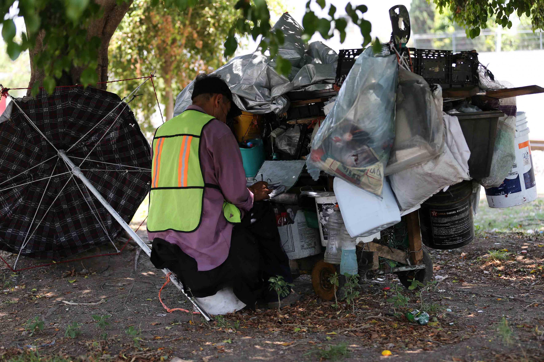 Persona en situación de calle, escribiendo sentado, enfrente del material de reciclado que ha recogido por la ciudad; mientras descansa a la sombra de un árbol.